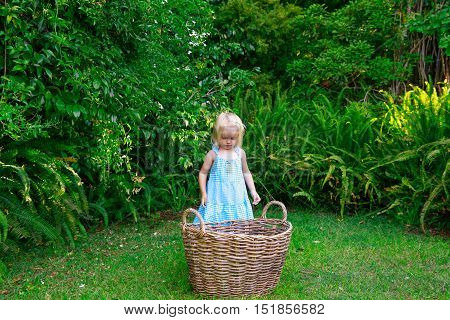Little Girl And Big Empty Laundry Basket Outdoors