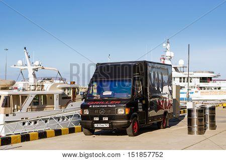 Sochi Russia - November 1 2015: Parked food truck - black truck-refrigerator Mercedes brought two barrels of beer at pier in Sochi seaport. Marine station complex Port. Krasnodarskiy kray Russia