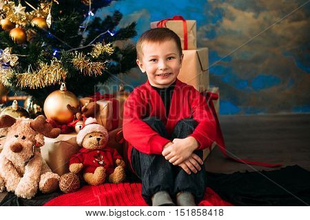 Portrait of adorable boy with christmas giftboxes
