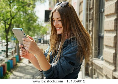 Happy girl on the street in the spring with a tablet computer in their hands.