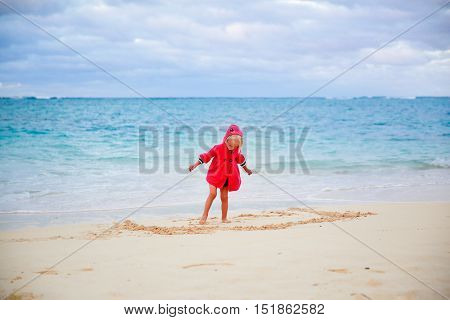 Little Girl In Red Coat Playing With Sand On The Beach