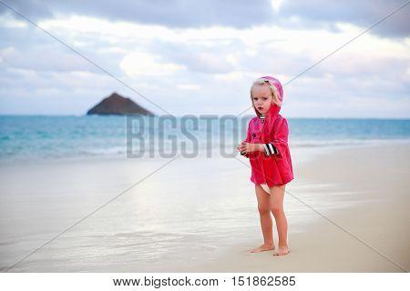 Little Girl In Red Rain Coat Walking On The Beach