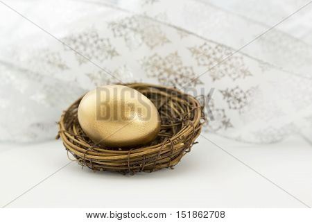 Gold nest egg sits as celebration and success symbol in front of swirl of white ribbons. Gift of financial security is symbolized.
