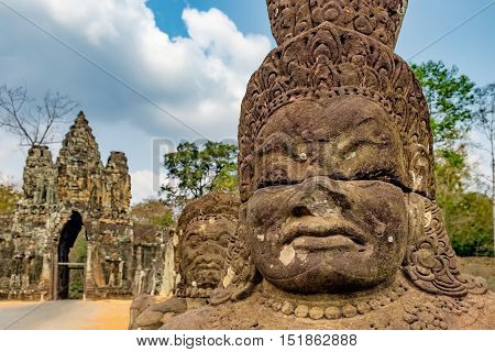 South gate to Angkor Thom and the faces of stone giants guarding the entrance Cambodia.