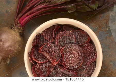 Fresh homemade beetroot chips in bowl photographed overhead on slate with natural light (Selective Focus Focus on the chips on the top)