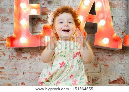 Little happy girl claps and sits near wall with big letters in studio