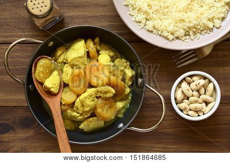 Chicken and dried apricot stew seasoned with turmeric cinnamon and honey accompanied by couscous and roasted almonds photographed overhead on dark wood with natural light