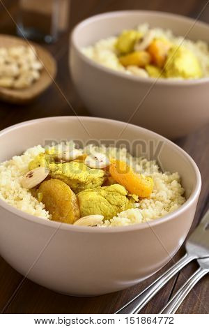 Chicken and dried apricot stew seasoned with turmeric cinnamon and honey served on couscous with roasted almonds photographed with natural light (Selective Focus Focus in the middle of the dish)