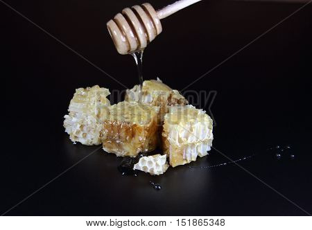 honey in honeycombs on a black background with a honey dipper