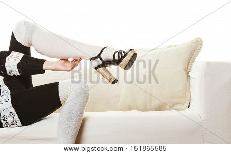 Fashionable woman legs. Girl in woolen white stockings black heeled shoes relaxing on sofa