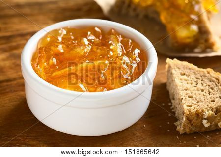 Orange jam in small bowl on wood with bread on the side photographed with natural light (Selective Focus Focus one third into the jam)