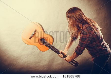 Rock music energy people feelings concept. Mad rock guitarist destroys his guitar.