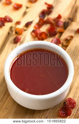 Homemade rose hip jam in bowl with dried rosehip on the side photographed on wood with natural light (Selective Focus Focus on the middle of the jam)