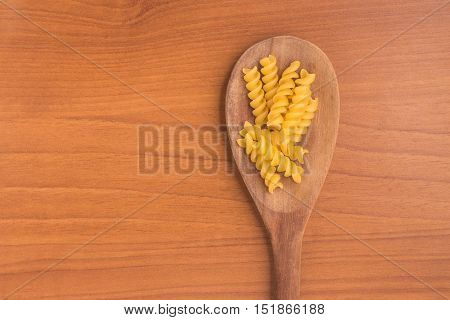 Fusilli into a spoon over a wooden table
