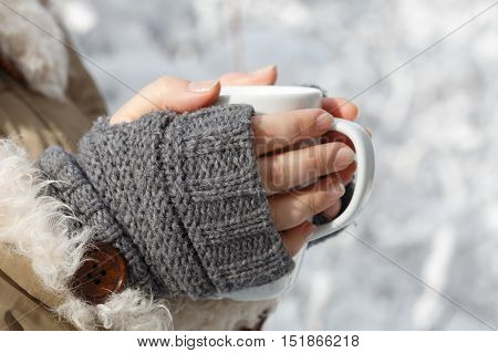 Women's hands in gray fingerless knitted mittens and coat with white fur holding white cup of tea at the background of snowy forest. Close up.