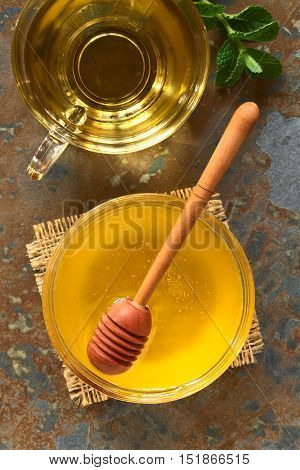 Honey in glass bowl with honey dipper fresh herbal tea above photographed overhead on slate with natural light