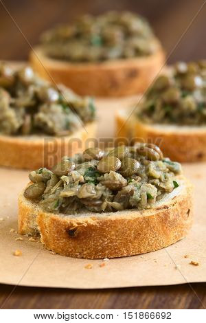 Lentil and parsley spread on bread slices served on paper photographed with natural light (Selective Focus Focus in the middle of the first canape)