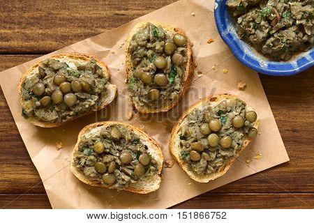 Lentil and parsley spread on bread slices served on paper photographed overhead with natural light (Selective Focus Focus on the spread)