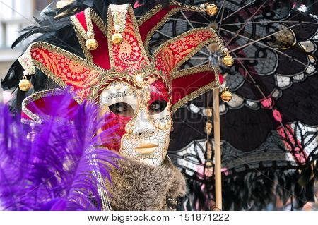 VENICE, ITALY - FEBRUARY 15, 2015: An unidentified person wearing a jester mask at Venice Carnival