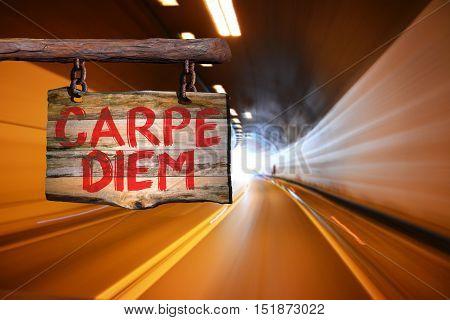 Carpe diem motivational phrase sign on old wood with blurred background