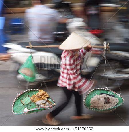A vietnamese farmer selling vegetable in market