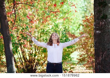 Young beautiful smiling teenager girl tosses colorful autumn leaves in park