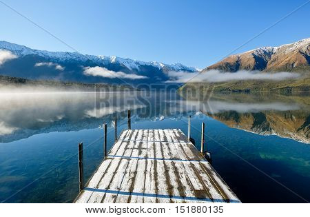 Dock and Mountains Reflected in Lake Rotoiti.  Nelson Lakes National Park, Southern Alps, New Zealand.