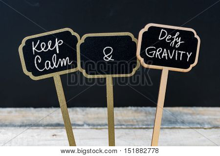 Keep Calm And Defy Gravity Message Written With Chalk On Mini Blackboard Labels