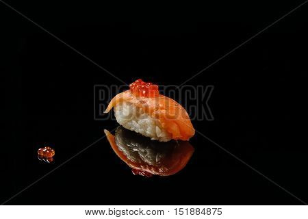 Sushi and red caviar of salmons on black acryle with reflection