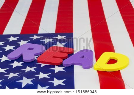 READ word on American flag emphasizes national education policy highlighting literacy and accountability. Concept focus on basic skills and learning as critical issues for schools parents pupils and nation.