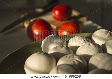 ravioli with tomato on the background of wood and a knife
