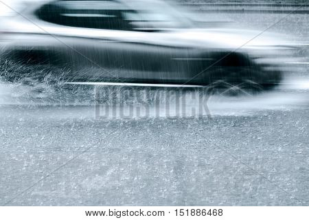 Car Driving At Speed Through Rain Puddles. Blured Motion.