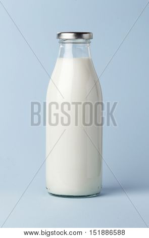 Filled milk bottle with a closed cap on blue background.