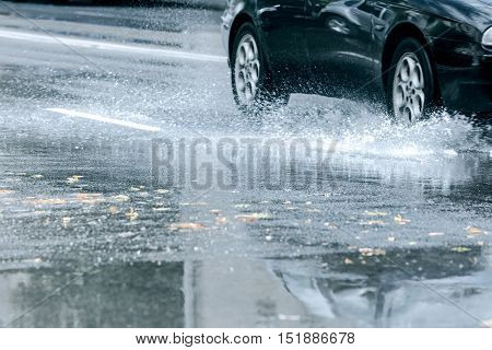 Black Car Driving Through Rain Puddle With Splashing Water From Wheels