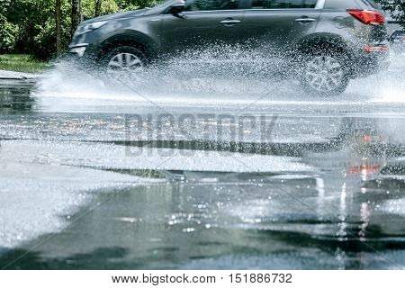 Black Car Driving Through Rain Puddle And Reflecting In It