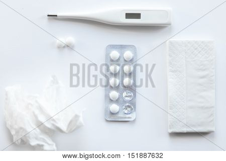 White desk with two round pills, taken from a foil case, thermometer, paper napkin and crumpled napkin on it. Top view, medicine concept photo