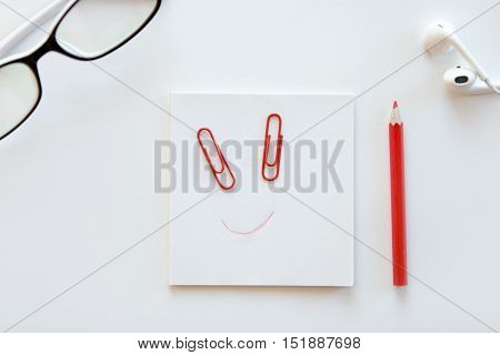 White desk with paper block with a drawn smile, clip eyes, glasses, earphones on it. Top view, copy space. Business concept photo