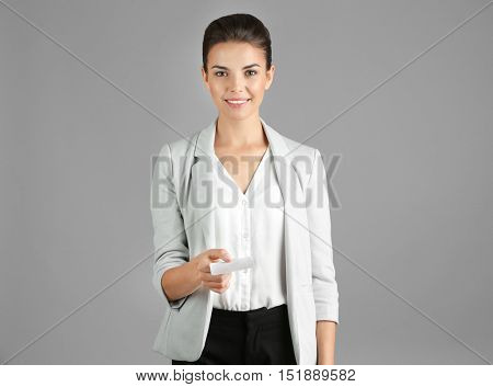 Beautiful businesswoman giving business card on gray background