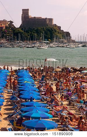 LERICI ITALY - JULY 16 2011: The Venere Azzurra beach crowded with bathers on a sunny day in july. In the background the castle and the port of Lerici Liguria Italy