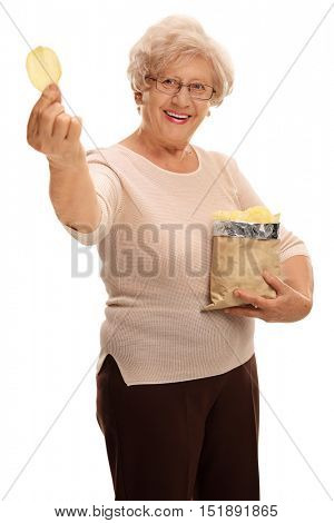 Cheerful mature woman holding a bag of potato chips and a single chip isolated on white background