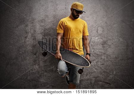 Skater holding a longboard and leaning against a rusty gray wall