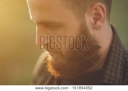 close-up of handsome young man with beard in background sunlight