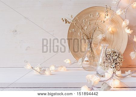 Soft home decor with burning lights on white wooden background. Interior.