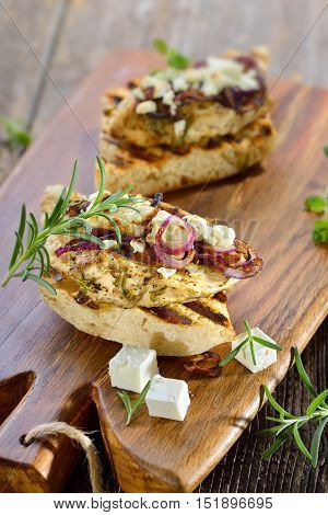 Toasted panini with grilled rosemary chicken breast fillet, baked feta cheese and roasted onion rings served on a wooden board