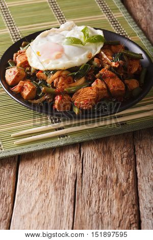 Spicy Stir-fry Chicken With Basil, Green Beans And A Fried Egg Close-up Vertical