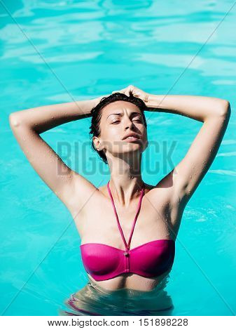 young sexy woman or girl with pretty face and wet hair swimming in pool with blue water sunny summer day outdoor
