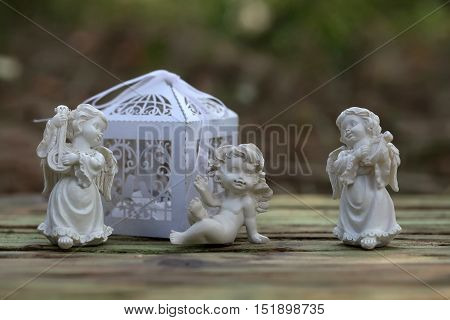 Beautiful cupids three porcelain valentines day decoration figurine and white paper decorative birdcage on wooden background