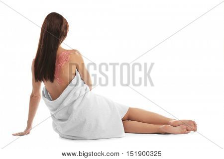 Young woman with nourishing scrub on back sitting on white background