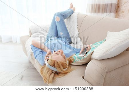 Young blonde girl with headphones and phone listening favorite music and lying on sofa