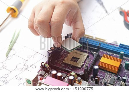 Man installing microprocessor on motherboard, close up